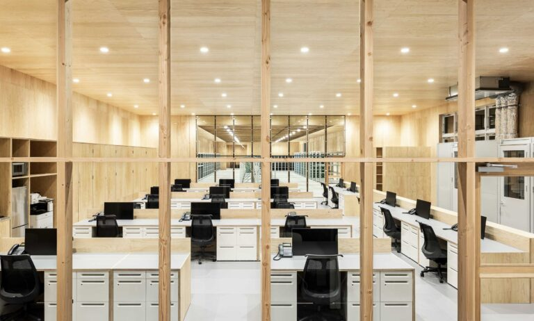株式会社三井の事務所風景 美しい木目の壁と天井に囲まれた広い空間にスタイリッシュなデスクとワークチェアが整列した写真